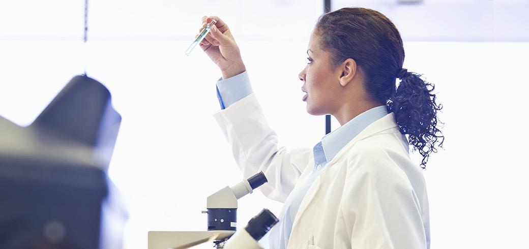 Un doctor în halat care inspectează un tub de testare
