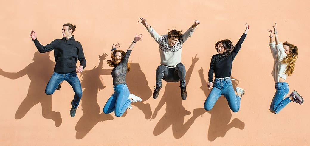 Un grup de prieteni sărind în aer, râzând și zâmbind.