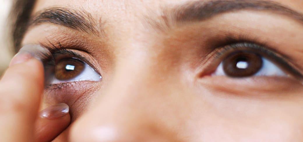 Imagine de aproape a ochiului unei tinere femei care își pune lentile de contact.